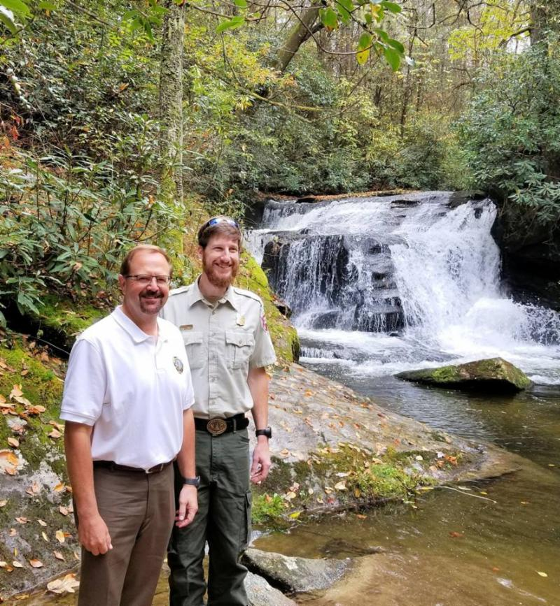 A Dupont State Forest ranger and Senator Chuck Edwards pose in front of a waterfall.
