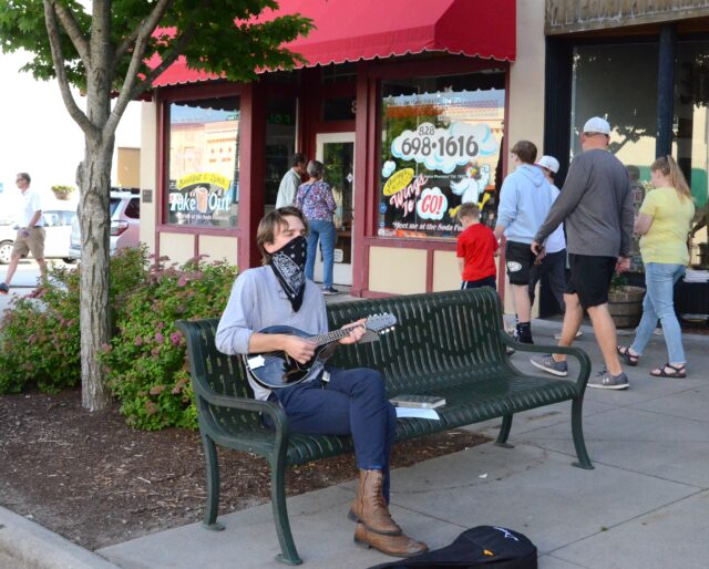 Andrew Torres, 21, plays mandolin as people stroll by Mike's on Main, at Fourth Avenue. Photo by Pete Zamplas.