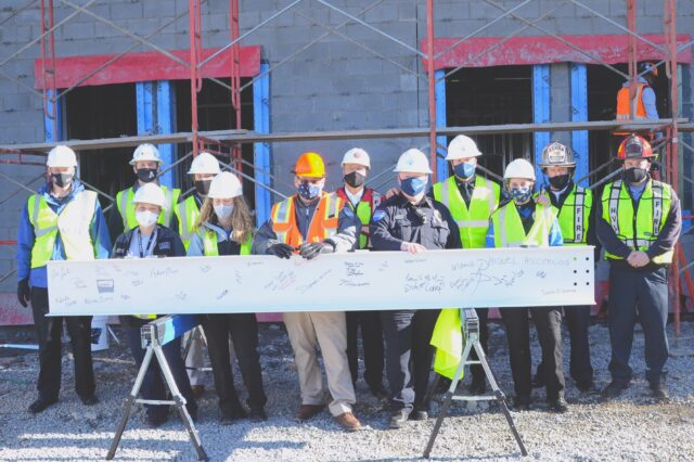 Hendersonville police, firefighters and city officials are in front of the new HPD station's ceremonial final beam that they autographed. Photo by Pete Zamplas.
