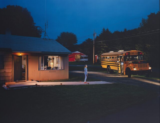 "The American photographer Gregory Crewdson portrays a child beckoning a bus driver early in the morning.  This is a chromogenic print mounted on aluminum, 47 5/8"" x 59 1/2"". This image is Courtesy of the Whitney Museum of American Art."