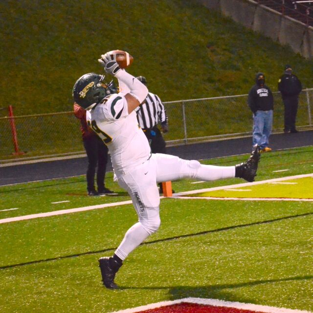 Rocket sophomore Russell Barnett — all 6-foot-3, 245 pounds of him — leans back to snatch a catch for Reynolds' first TD against Asheville. Barnett, a defensive lineman, was an eligible tight end. His score turned around the game, as ACR swiped the lead. Photo by Pete Zamplas.