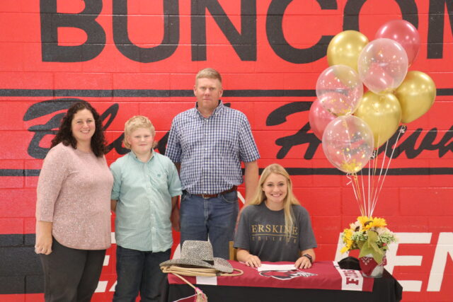 Senior Clara Hale prepares to sign with Erskine College as her family dad, Matthew, brother, Jake, and mom, Elizabeth Hale watches. Photo by Clint Parker.